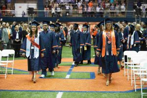 students walk with school of education graduation